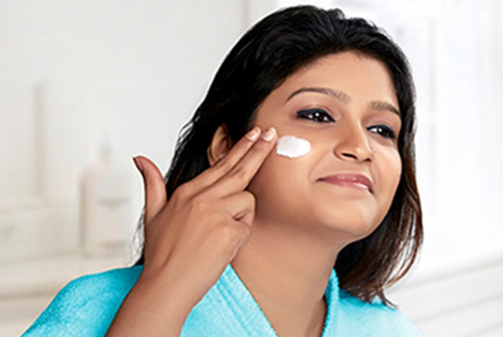 Woman applying face cream.